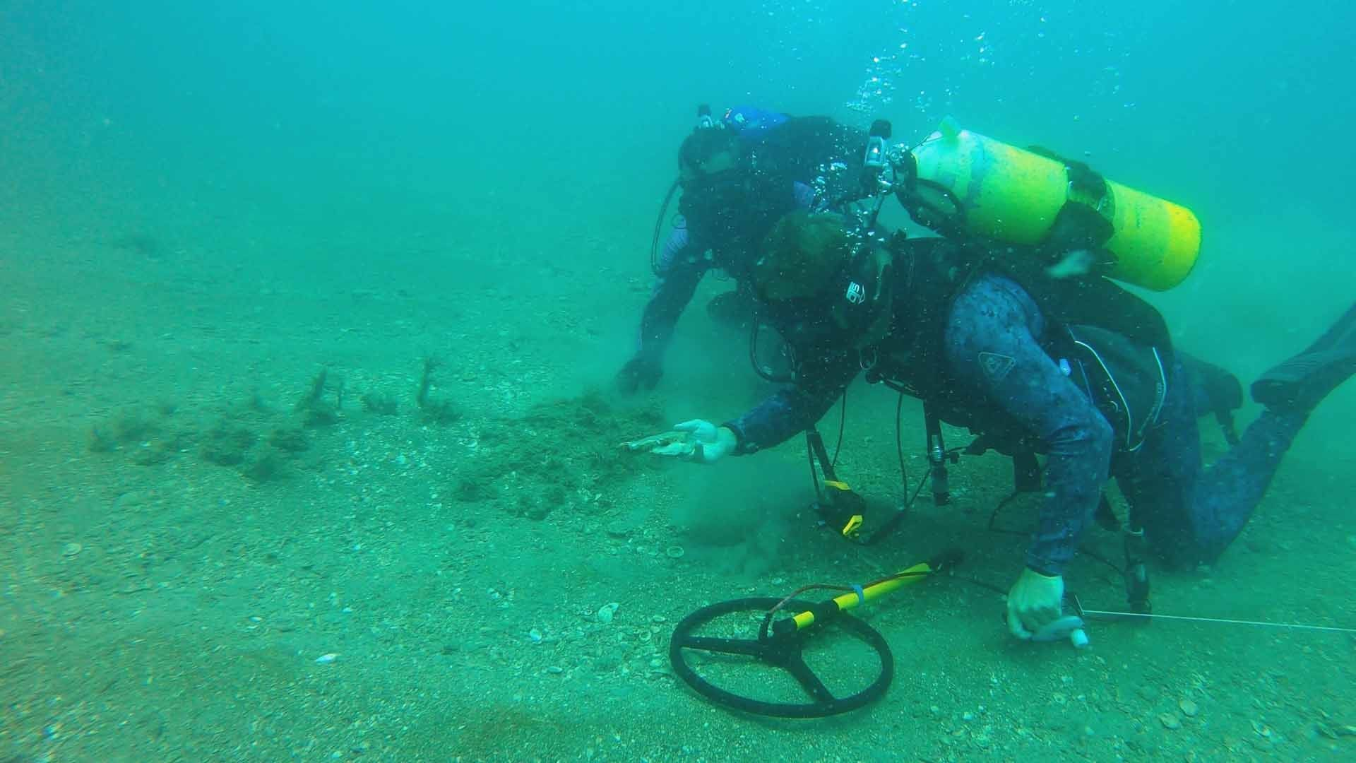 Seafarer-Exploration-4-Diver-metal-detecting-and-examining-and-artifact-on-the-ocean-floor-with-great-visibility